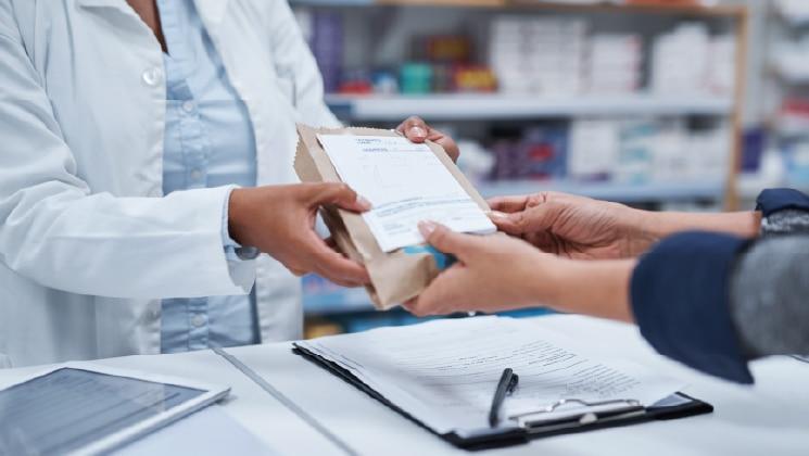 Close up of pharmacist handing over a prescription